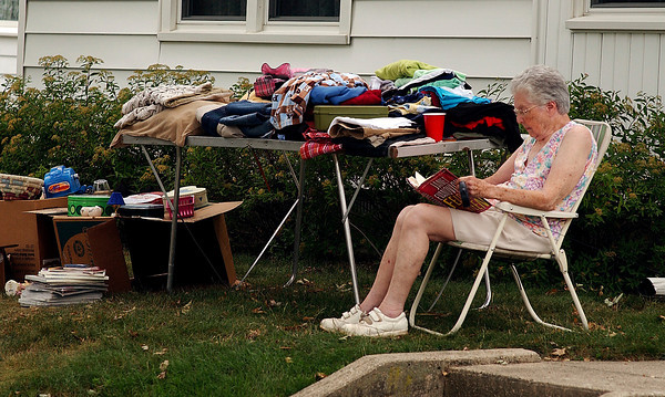 Peggy Stephens enjoys her book as she sits out front of her house during the town-wide rummage sale Saturday as part of the Lapel Village Fair.