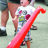 Two-year-old Connor Shaw of, Carmel, reacts to seeing the inflatable man that was a lot larger then his inflatable bat during the Lapel Village Fair Saturday.