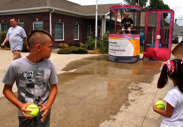 Caleb Johns, 10, winds up to try to hit the target at the Lapel Medical Arts dunk tank at the Lapel Village Fair.