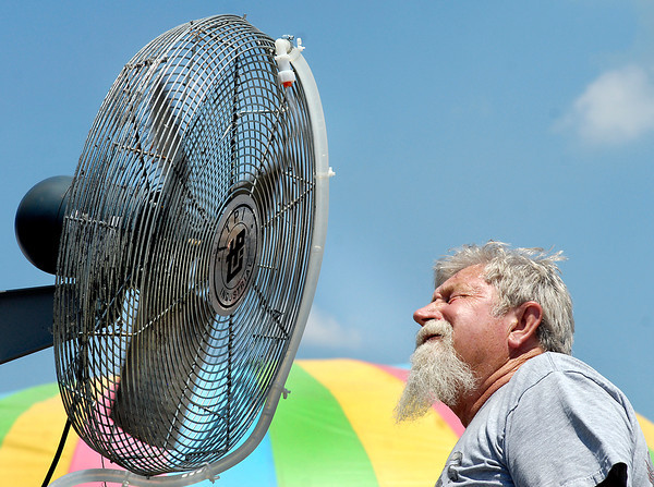 Alexandria Kiwanis member Kenny Summers tests out the misting fan he just installed on the 4-H grounds to check the amount of misting, and to cool off.  The Kiwanis put up four misting fans around the fair grounds Monday to help people keep cool.