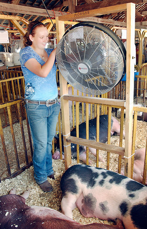 Cheyenne Morgan, 15, adjusts the large fan in her hog pin to help keep her six pigs cool at the 4-H Fair.