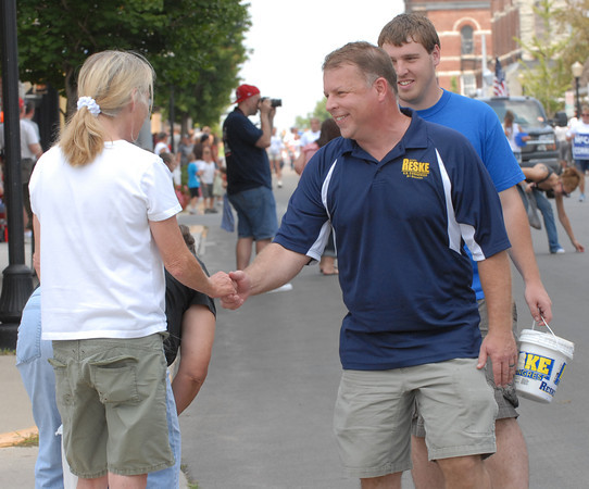 Democratic congressional candidate Scott Reske shakes hands with a parade onlooker.