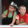 Two youngsters wave from an Alexandria Fire Department truck at the 2012 Madison County 4-H Fair Parade. The event took place Sunday afternoon in downtown Alexandria to kick off the annual fair.