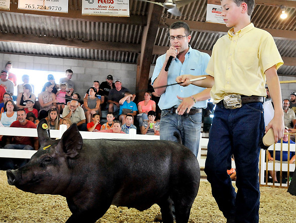 John P. Cleary    The Herald Bulletin<br /> Swine judge Miles Tdenyes gives comments as Chandler Lowes parades his champion heavy weight division Cross Bred Barrow around the show ring Monday.