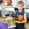 Don Knight | The Herald Bulletin<br /> Nathaniel Miller, 9, holds his Old English Rooster and his trophy after winning the rooster crowing contest at the 4-H Fair on Tuesday. Three roosters tied for the win and Miller's bird won in sudden death overtime.