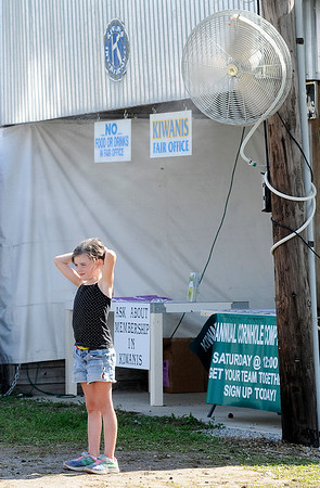 Don Knight | The Herald Bulletin<br /> Breeleigh Petty, 7, gets relief from Wednesday's high heat and humidity by cooling off under a misting fan at the 4-H Fair.