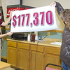 Volunteers Tina McLain and Donna Ritzen unveil how much money was raised during the Chadron State Foundation's fall fund-raising campaign. (Photo by Justin Haag)