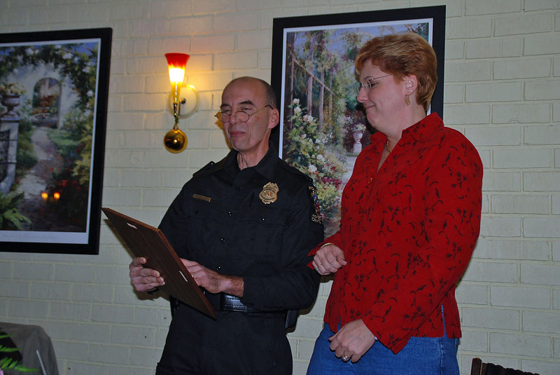 Assistant Chief Drew Tracey awards retirement plaque to Jean.