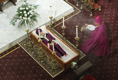 During the solemn vespers service Nov. 16, Archbishop Wilton D. Gregory, right, censes the body of Archbishop John F. Donoghue, the fifth archbishop of Atlanta.