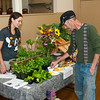 Laurence Schuler tries out the heirloom tomotoes offered by Hillary Jensen-Bergren from Peace of the Earth Farms