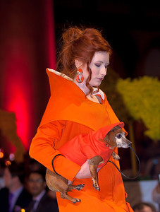 FIDM Model Chelsea Taylore. The bright orange hooded cape for model dog Kiki was created by Ralph Prado, born in the Philippines.
