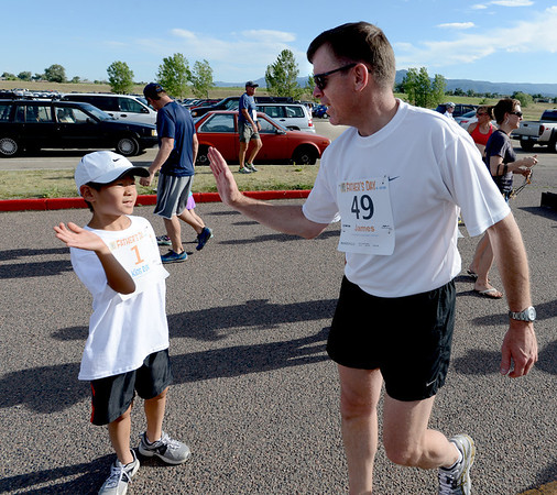 """James Knapp has a high five for his son, Justin, 8, after the pair finished the 1K Fun Run as part of the Fathers' Day activities at the Boulder Reservoir on Sunday.<br /> For more photos of the races, go to  <a href=""""http://www.dailycamera.com"""">http://www.dailycamera.com</a>. or  <a href=""""http://www.timescall.com"""">http://www.timescall.com</a>.<br /> Cliff Grassmick / June 17, 2012"""