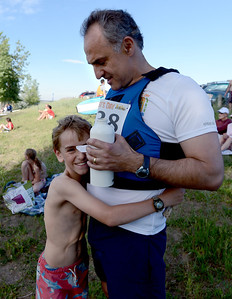 Charlie Sutcliffe, 10, has a hug for his dad, Nick, after dad finished the paddleboard race as part of the Fathers' Day activities at the Boulder reservoir on Sunday. For more photos of the races, go to www.dailycamera.com. or www.timescall.com. Cliff Grassmick / June 17, 2012