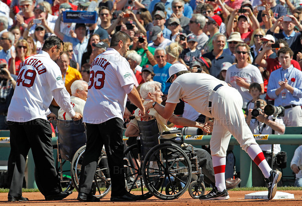 BOSTON -- Boston Red Sox hitting coach Dave Magadan, right, speaks with Red Sox alumnus Johnny Pesky, second from right, as Pesky and Bobby Doerr, second from left, are wheeled off the field by Tim Wakefield, left and Jason Varitek at the end of a special pregame ceremony celebrating Fenway Park's 100th anniversary on Friday, April 20, 2012. (Brita Meng Outzen/Boston Red Sox)