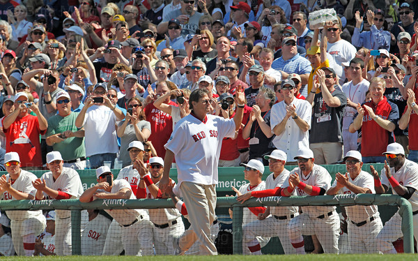 BOSTON -- Former Boston Red Sox catcher and Hall of Famer Carlton Fisk, center, waves as he walks to his position as current Red Sox, from left, Jon Lester, John Lackey, Nick Punto, Felix Doubront, Mike Aviles, Ryan Sweeney, Jacoby Ellsbury, Adrian Gonzalez, manager Bobby Valentine and David Ortiz applaud on the dugout steps during the special pregame ceremony celebrating the 100th anniversary of Fenway Park on Friday, April 20, 2012. (Brita Meng Outzen/Boston Red Sox)