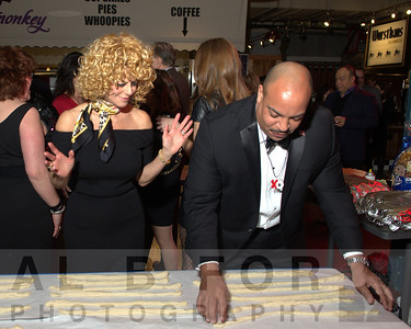 Sharon Pinkenson (Executive Director, Greater Philadelphia Film Office) watches as Seth Williams, Philadelphia District Attorney  attempts to Twist a Pretzel.  The Valentine to the Market Gala, Saturday, February 23, 2013. ( Al B. For / Philly.com )