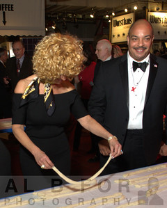 "Celebrity ""Twist-off"" begins in the Center Court of the Reading Terminal. Sharon Pinkenson (Executive Director, Greater Philadelphia Film Office) attempting to Twist a Pretzel as Seth Williams, Philadelphia District Attorney, watches on. The Valentine to the Market Gala, Saturday, February 23, 2013. ( Al B. For / Philly.com )"