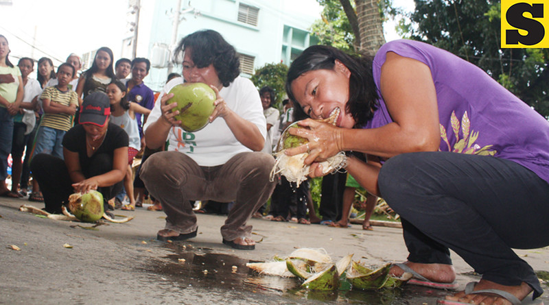 CAGAYAN DE ORO. Residents from the city's hinterland barangays show off their skills on Tuesday in peeling a coconut using only their teeth. The contest was one of the highlights of the agro-industrial fair as part of the city's fiesta celebration. (Joey P. Nacalaban)