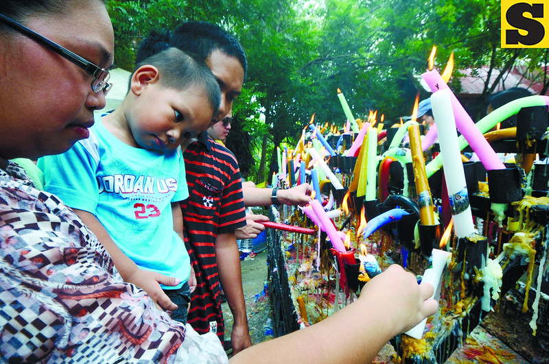 SAY A LITTLE PRAYER FOR ME. A family lights colored candles and prays to the Virgin Mary at the Monastery of Holy Eucharist in Barangay Lindogon to commemorate the birth of Jesus Christ's mother. (Photo by Alex Badayos of Sun.Star Cebu)