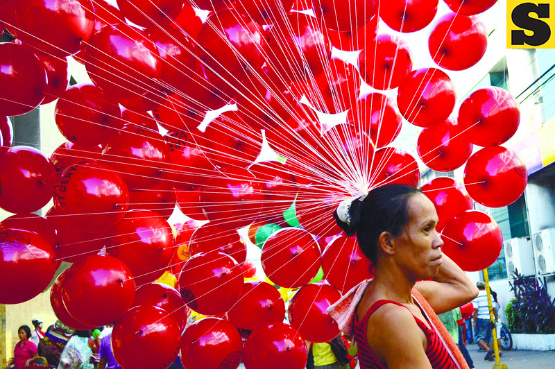FIESTA ESSENTIALS. No fiesta is complete without balloon, and enterprising individuals know kids will find them irresistible, especially if they come in fiery red.  Balloon vendors station themselves on the Sinulog parade route and near the Basilica del Sto. Nino during the Sinulog. (Sun.Star Photo/Alan Tangcawan)
