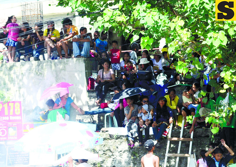 CEMETERY WALLS.  Spectators find the walls of the Carreta Cemetery a perfect place to get a good view of the street dancing on Gen. Maxilom Avenue. (Sun.Star Photo/Allan Cuizon)