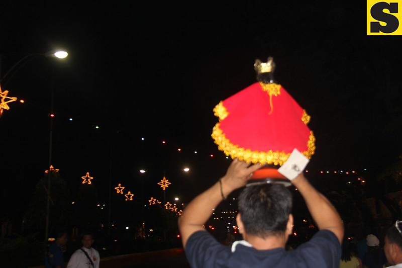 A man carries a Sto Nino image