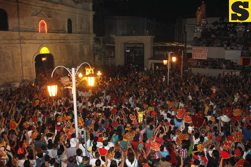 People wave their hands as Sto Nino enters Basilica
