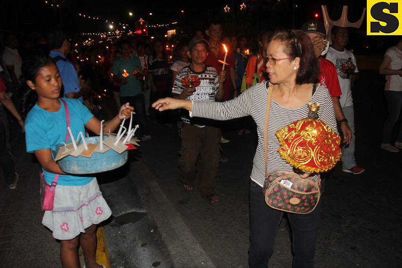 A woman buys a candle during Walk with Jesus in Cebu City