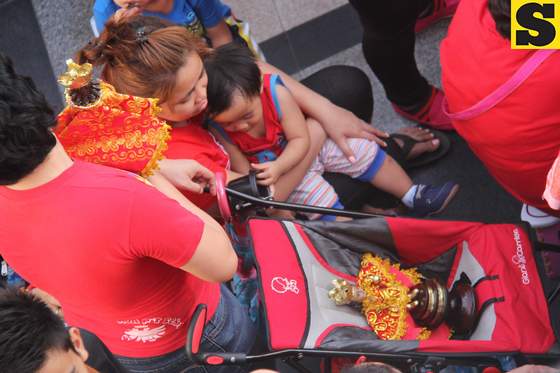 Mother and child, with Sto Nino image on stroller