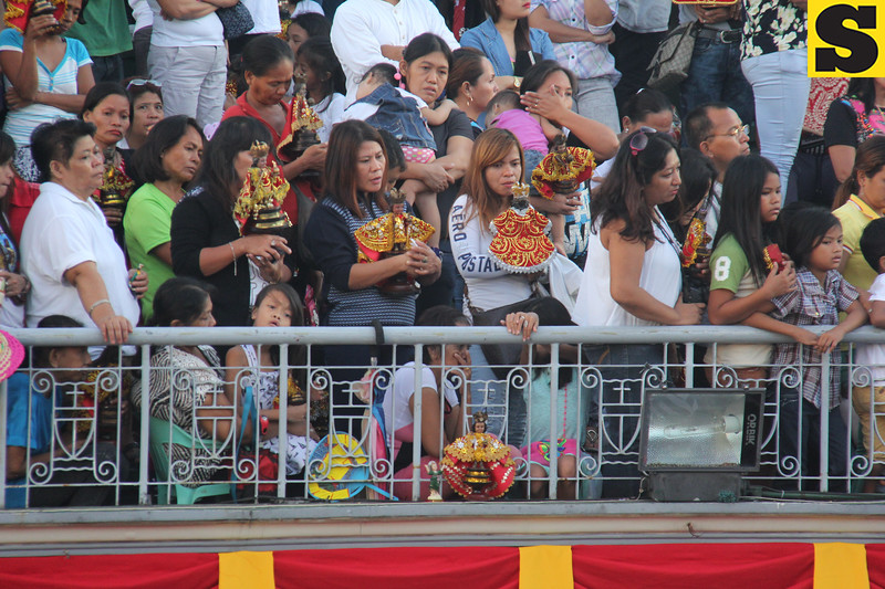 Women attending mass with their Sto Nino icons