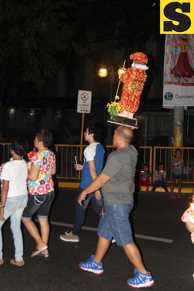 A man carries a Sto Nino image