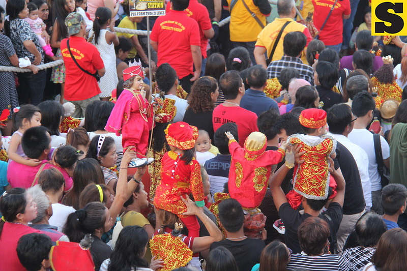 Child wearing Sto Nino costume during mass
