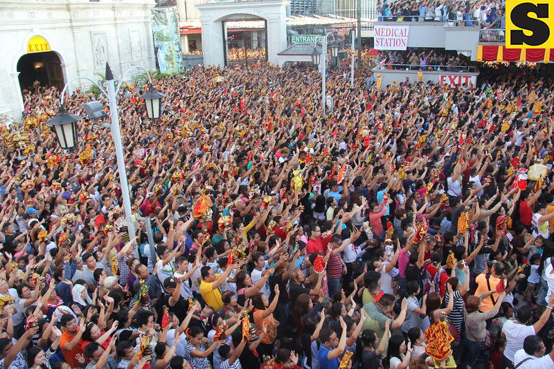 People at Sto Nino wave their hands as they sing Bato Balani