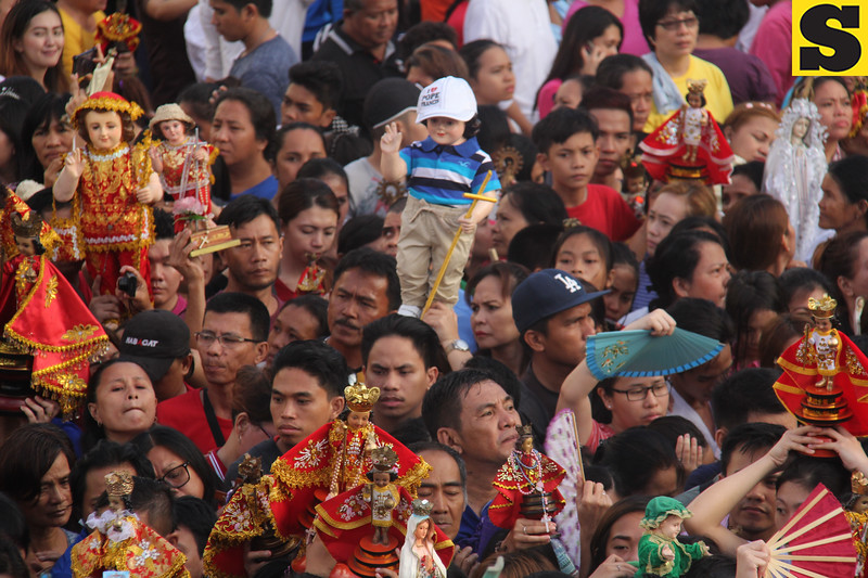 Devotees carrying icons of Sto. Nino and Mama Mary