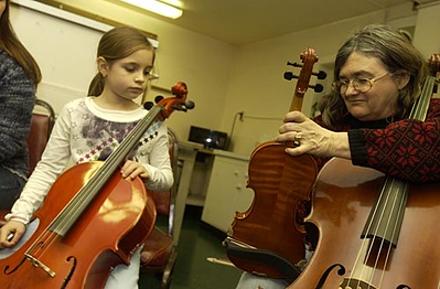 Record-Eagle/Garret Leiva<br /> Chris Williams, right, tunes a violin in between songs as Carmin Jamison, 8, looks on during a fiddle jamboree Saturday evening in the kitchen at Gilbert Lodge at Twin Lakes Camp. Williams says the fiddle jamboree, which is open to a variety of string instruments and hand drums, meets before the Bayside Travellers dances held the second Saturday of the month. For more information on joining the fiddle jamboree, call Williams at (231) 421-1278.