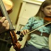 Record-Eagle/Garret Leiva<br /> Michala Jamison, 11, of Traverse City, joins the fiddle jamboree Saturday evening in the kitchen at Gilbert Lodge at Twin Lakes Camp. Jamison says she has been playing the violin since she was 6 years old.