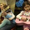 Record-Eagle/Garret Leiva<br /> Elizabeth Chavez, left, of Traverse City, plays the guitar with her daughter Estela, 2, on her lap while her other daughter, Santina, 5, strums along on her jeweled pink acoustic six string during the fiddle jamboree.