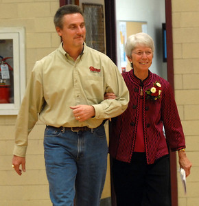 Former Glenbard East Athletic Director Noree Mares makes her way through the gym alongside her former Assistant Gregg Koeller during the fieldhouse dedication in which they named the fieldhouse after her prior to the boys basketball game against Glenbard North Friday December 9, 2011.    Staff photo by Erica Benson   |   snapshots.mysuburbanlife.com/1376804