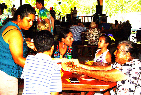 A family gets ready to dine as live mariachi music blares from the pavilion stage.