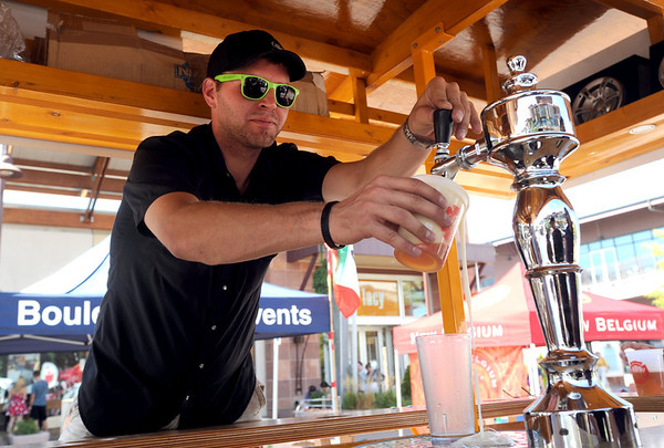 """Lucas Allen of Oskar Blues Brewery, pours a glass of beer during the festival.<br /> Colorado firefighters were celebrated with the first annual Fight Fire with Beer Festival on the 29th Street Mall plaza on Saturday.<br /> For more photos and a video of the festival, go to  <a href=""""http://www.dailycamera.com"""">http://www.dailycamera.com</a>.<br /> Cliff Grassmick  / September 15, 2012"""