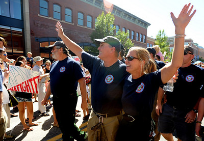 Bob Oliver, left, and Melody Pray, both of Boulder Mountain Fire District, walk in the parade down Pearl Street on Sunday. A special parade  for the Fourmile firefighters was held during the Boulder Green Streets celebration. For a video of the parade, go to www.dailycamera.com. Cliff Grassmick / September 19, 2010