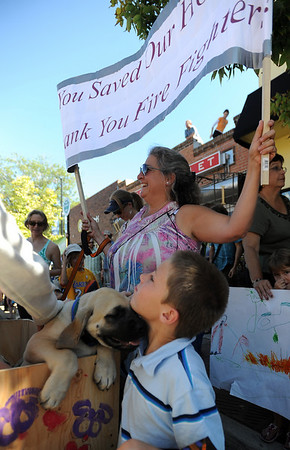 "Sam Berry plays with one of the rescued puppies belonging to Mira Hatland, holding the sign in the background.<br /> A special parade  for the Fourmile firefighters was held during the Boulder Green Streets celebration.<br /> For a video of the parade, go to  <a href=""http://www.dailycamera.com"">http://www.dailycamera.com</a>.<br /> Cliff Grassmick / September 19, 2010"