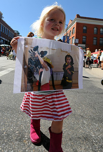 Maisie Creamer, 3, walks in the parade with a picture she brought to honor the firefighters. A special parade  for the Fourmile firefighters was held during the Boulder Green Streets celebration. For a video of the parade, go to www.dailycamera.com. Cliff Grassmick / September 19, 2010