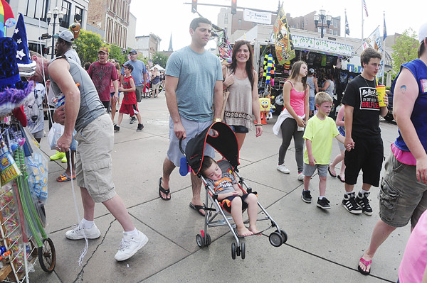 Trenton Aubel, 2, of Shenango Township sleeps through the festival while walking with his parents, Timothy and Kaycee. — Tiffany Wolfe
