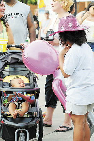 Tiffany Wolfe/NEWS Ten-month-old Niko Brown enjoys the compaby of Aubrey Phipps, 7, as their parents talks at Saturday's Fireworks Festival. Both families are from New Castle.