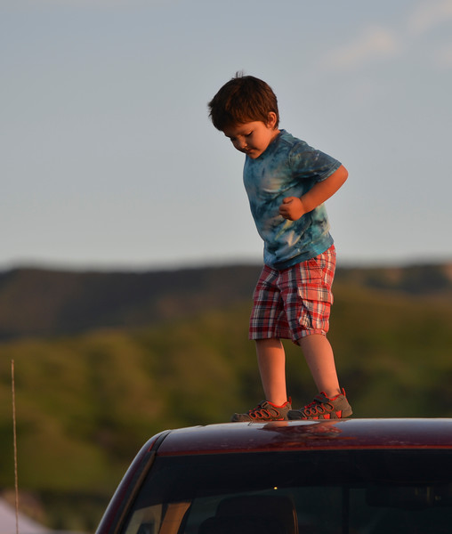 Justin Sheely | The Sheridan Press<br /> Four-year-old Tyke Small of Lame Deer, Montana, plays on top of his father's truck during the annual Independence Day celebration at the Big Horn Equestrian Center Wednesday, July 4, 2018.