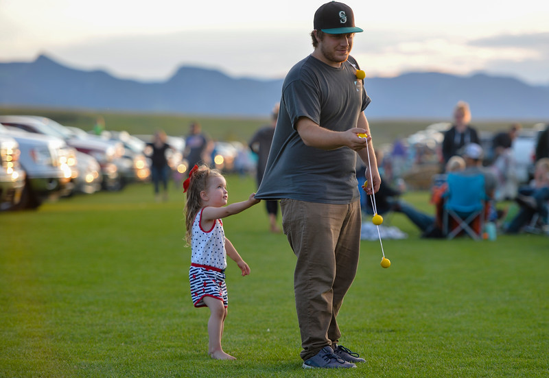 Justin Sheely | The Sheridan Press<br /> Chase Walton tries to play ladder ball as his daughter Aura Creech, 3, tugs on his shirt during the annual Independence Day celebration at the Big Horn Equestrian Center Wednesday, July 4, 2018.