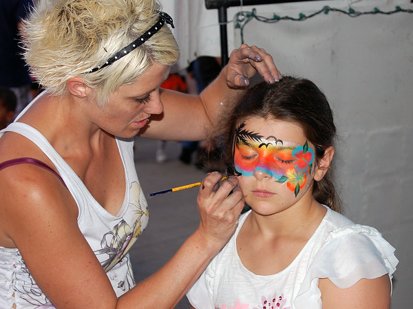 Sam Luptak Jr. | NEWS<br /> <br /> Ella Snyder, 9, sits patiently as an artist finishes up a full beach scene she is having painted on her face Saturday.