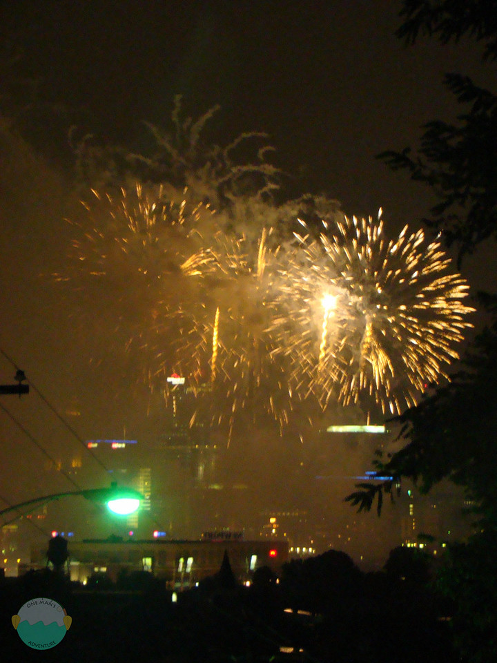 More fireworks going off with Newport levee in the foreground and downtown Cincinnati behind the fireworks.