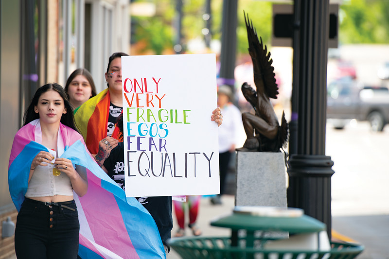 "Matthew Gaston | The Sheridan Press<br>A young woman carries a sign reading, ""ONLY VERY FRAGILE EGOS FEAR EQUALITY"" down Main Street for Sheridan's first LGBTQIA pride march Saturday, June 22, 2019."